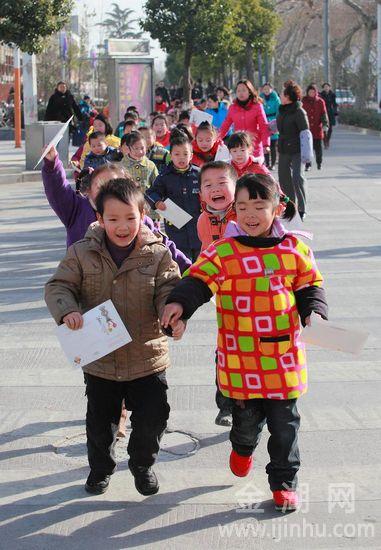 """参与""""迎新年•邮贺卡•送祝福""""活动的小朋友们,排队走在街头,心情特别舒爽"""